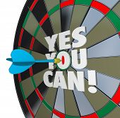 The importance of confidence and a positive attitude illustrated by a dart hitting the words Yes You Can on the bulls-eye of a dartboard