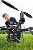 Young technician fixing camera on spy drone at park