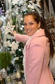 Young woman shopping glittering Christmas decorations in pink coat