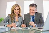 Two pleased mature business people smiling at camera analyzing a graphic at office