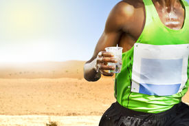 stock photo of transpiration  - Thirsty transpiring runner in the desert with cup of water