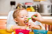 Child Girl Eats Porridge From A Spoon On Kitchen. Use It For Child, Healthy Food Concept