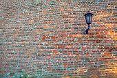 Lantern on a wall with bricks