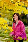 pic of biracial  - Little biracial asian girl standing amongst bright autumn leaves - JPG