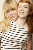red and blond haired girls friends laugh and hug