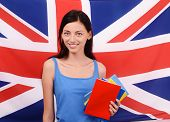 Learn English. Beautiful student holding books, red blank book cover.