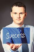 caucasian businessman is holding success text in hands