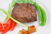 meat food : roast beef fillet mignon served on white plate with apples dill and tomatoes isolated ov