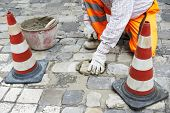 stock photo of banquette  - mason worker making sidewalk pavement with stone blocks - JPG