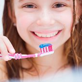 Cute girl brushing teeth in bath close-up