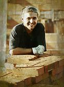 Worker on building site with brick posing and smiling