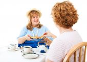 Two mature ladies enjoying a tea party together.  White background.