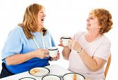 Two mature ladies having tea together and laughing.