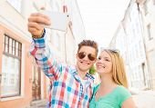 travel, vacation, technology and friendship concept - smiling couple with smartphone in city