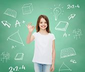 advertising, school, education, childhood and people - smiling little girl in white t-shirt showing