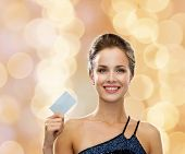 shopping, wealth, luxury, holidays and people concept - smiling woman in evening dress holding credi