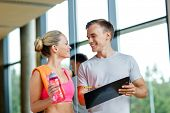 fitness, sport, exercising and diet concept - smiling young woman with personal trainer after traini