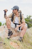 Portrait of a hiking man sitting on mountain terrain