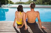 Rear view of a young couple sitting by swimming pool on a sunny day
