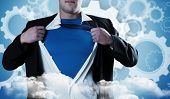 Businessman opening his shirt superhero style against white wheels and cogs on blue