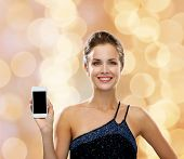 technology, communication, advertisement and people concept - smiling woman in evening dress holding