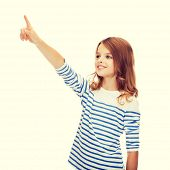 education, school and virtual screen concept - cute little girl pointing in the air or virtual screen