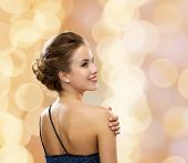 people, holidays and glamour concept - smiling woman in evening dress over black background over bei