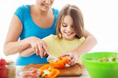 family, child, cooking and home concept - smiling little girl with mother chopping pepper in the kit