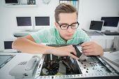 Technician working on broken computer in his office