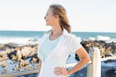 Casual woman smiling by the sea on a sunny day