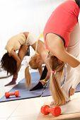 Three women exercising at the gym, bending, hugging leg.