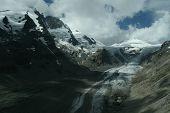 Glacier Melting In The Summer Between Alpine Peaks