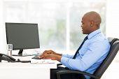 black business man at desk typing on keyboard