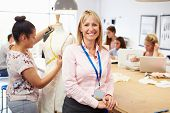 Portrait Of Teacher Helping College Fashion Students