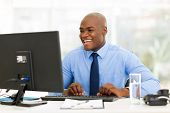 cheerful african american businessman working on computer
