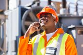 afro american electrical engineer talking on smart phone in electricity power plant