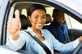 beautiful female african learner driver with instructor giving thumb up