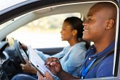 african american driving instructor inside a car with student driver