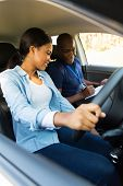 smiling young african girl taking lessons from driving instructor