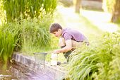 Boy Fishing In Pond With Net And Jar