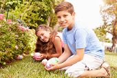 Two Children Having Easter Egg Hunt In Garden