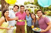 Group Of Friends Having Party In Backyard At Home