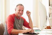 Portrait Of Senior Man Using Computer At Home