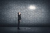 Asian man standing in front of a puzzle wall. Concept of mystery, problem, solution.