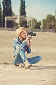 Young Woman Shooting Video With Old Analog Camera