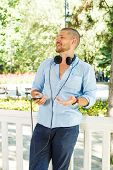 Handsome Guy In The Light Blue Shirt Posing With Headphones And A Phone In His Hand