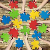 Group of Hands Holding Jigsaw Puzzle