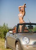 Постер, плакат: Beautiful and sexy woman in a convertible car