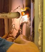 image of pipe-welding  - The plumber makes gas welding of a pipe in the apartment - JPG