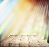 Wooden table top on sunny bokeh background